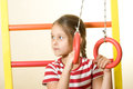 Exercise on the gymnastic rings little girl athlete preparing to do Stock Photos