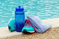 Exercise and hydration concept blue water bottle with running shoes towel by pool copy space Stock Images