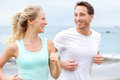 Exercise running couple jogging on beach talking and training as part of healthy lifestyle two fit runners happy and Royalty Free Stock Photos