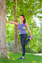 Exercise woman stretching hamstring leg muscles during outdoor running workout smiling happy sport fitness model in city park Stock Photos