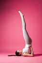 Exercise young woman doing candle position studio shot pink background Royalty Free Stock Photo