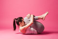 Exercise young woman in relax position studio shot pink background Royalty Free Stock Images