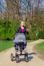 Exercising with a baby buggy active attractive mother is Stock Photos