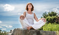 Exercising outside for radiant 50s yoga woman sitting on ston Royalty Free Stock Photo