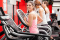 Exercising on a treadmill pretty girl working out in at the gym and smiling Stock Images