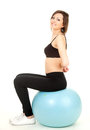 Exercising young woman sitting on big blue ball Stock Image
