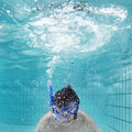 Exhaling underwater man wearing driving glasses and a snorkel exhailing through the tume in an indoor swimming pool Royalty Free Stock Photos