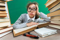 Exhausted or bored young student around a lots of books. Royalty Free Stock Photo