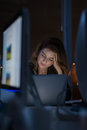 Exhausted business woman sitting at workplace in dark office Stock Photo