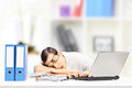 Exhausted businessman sleeping on a desk in his office young Stock Photos