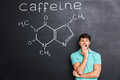 Exhausted fatigued man yawning over chalkboard with drawn caffeine molecule
