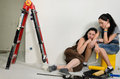 Exhausted female friends doing renovations taking a break and closing their eyes as they relax together floor to recover their Royalty Free Stock Image