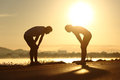 Exhausted and tired fitness couple silhouettes at sunset side view of a Stock Photo