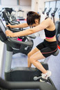 Exhausted woman on the exercise bike Royalty Free Stock Photo