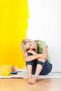 Exhausted woman taking a break from decorating her house and painting the walls sitting on the floor with her head on her arms and Stock Photography