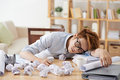 Exhausted worker man sleeping at the table with many documents and crumpled paper Stock Photos