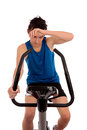 Exhausted after workout on exercise bike male teenager wiping brow fitness an white background Royalty Free Stock Photography