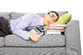Exhausted young businessman sleeping on a couch with many docume document isolated white background Stock Photography