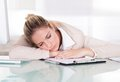 Exhausted young businesswoman sleeping at her workplace Royalty Free Stock Image