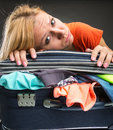 Exhausted young woman packing luggage for vacations Royalty Free Stock Photo