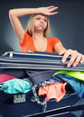 Exhausted young woman packing luggage for vacations Royalty Free Stock Photography
