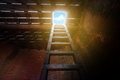 Exit of a dark room, wood ladder from basement up to see the sky Royalty Free Stock Photo