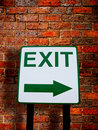 Exit direction sign on brick wall background Stock Photos