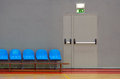 Exit door emergency next to a row of blue sits in a sports pavilion Royalty Free Stock Photos