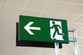 Exit sign at airport green with man running image and arrow terminal three malaga malaga andalusia spain western europe Stock Image