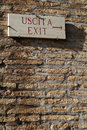 Exit sign on a brick wall in the roman colosseum Stock Photos