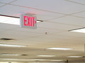 Exit sign on ceiling indoor shows way to the Royalty Free Stock Image