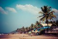 Exiting anjuna beach panorama on low tide with white wet sand and green coconut palms goa india Royalty Free Stock Photo