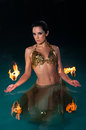 Exotic belly dancer with fiery palm toches wet standing waist deep in blue water she is wearing a gold costume and holding flaming Stock Photo