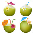 Exotic coconut cocktails young green coconuts with drinking straws cocktail umbrellas and tropical flowers isolated on white Stock Image