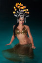 Exotic dancer with fire headdress portrait of an wet belly standing waist deep in blue water wearing a a gold costume a Royalty Free Stock Images