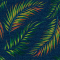 Exotic leaf seamless print on denim backdrop. Bright palm leaves on a dark blue background, color graphics, blue jeans