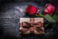 Expanded roses wrapped present box on wood board holidays concept Royalty Free Stock Image
