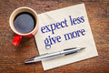 Expect less give more advice motivation or self improvement concept handwriting on a napkin with a cup of coffee Stock Image