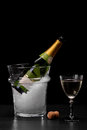 An expensive bottle of champagne in a transparent bucket filled with ice on a black background. Celebration concept. Royalty Free Stock Photo