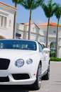 Expensive sports car with tropical background a beautiful white a colorful showing palm trees and south florida architecture on a Royalty Free Stock Image