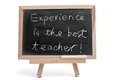 Experience is the best teacher saying written on blackboard over white background Royalty Free Stock Images