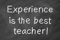 Experience is the best teacher written by white chalk on blackboard Royalty Free Stock Image