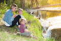 Experience nature mother and her two little children sitting at the shore of a small river in sweden and watching beavers Stock Photography