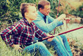 Experienced boy teenager and father fishing togethe Royalty Free Stock Photo