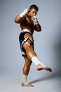 An experienced fighter kickboxer with a raised foot full height Stock Image