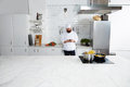 Experienced male chef cook standing on big modern kitchen while using smart phone Royalty Free Stock Photo