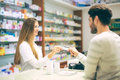 Experienced pharmacist counseling male customer in pharmacy