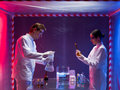 Experimental glassware in the lab two scientists a men and a woman working with chemicals a containment tent Royalty Free Stock Photo