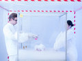 Experimenting with liquid nitrogen in containment tent two scientists a a men and a woman a sterile chamber Stock Image