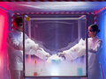 Experimenting with liquid nitrogen in protective enclosure two scientists a men and a woman mixing chemicals a sterile chamber Royalty Free Stock Images